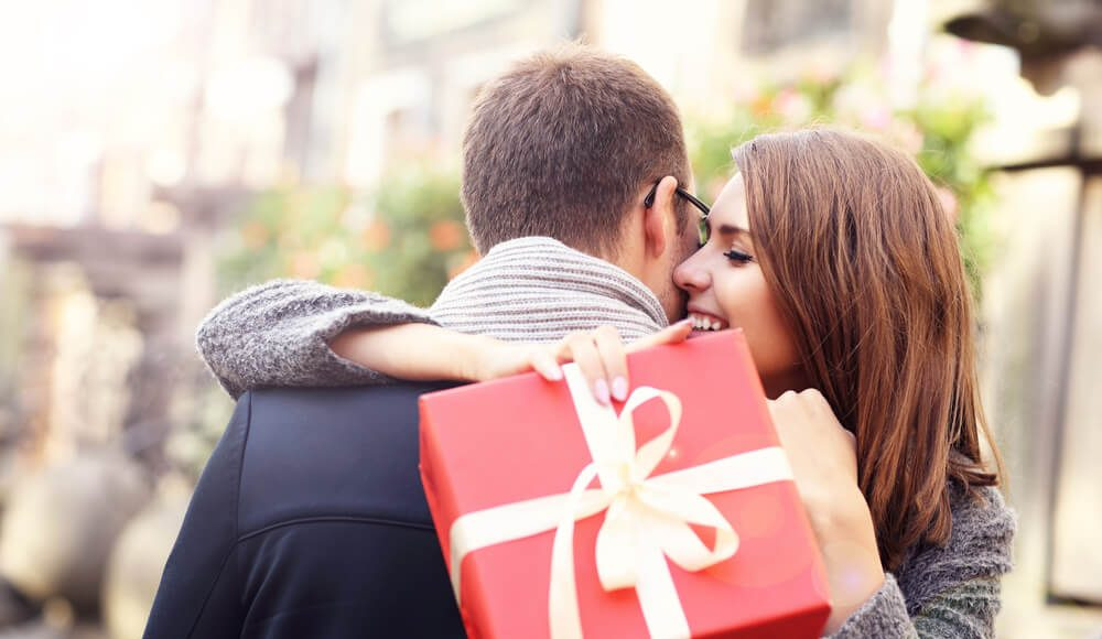 a girl holds gift and hugging his man