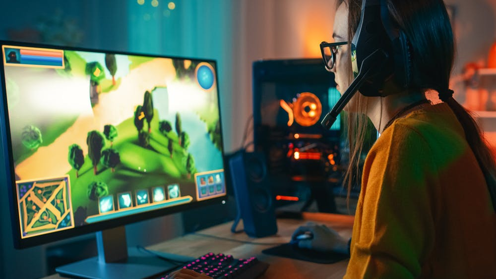 a girl playing game infront of computer