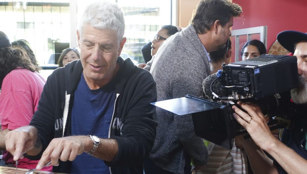 Anthony Bourdain et al. sitting at a table with a plate of food