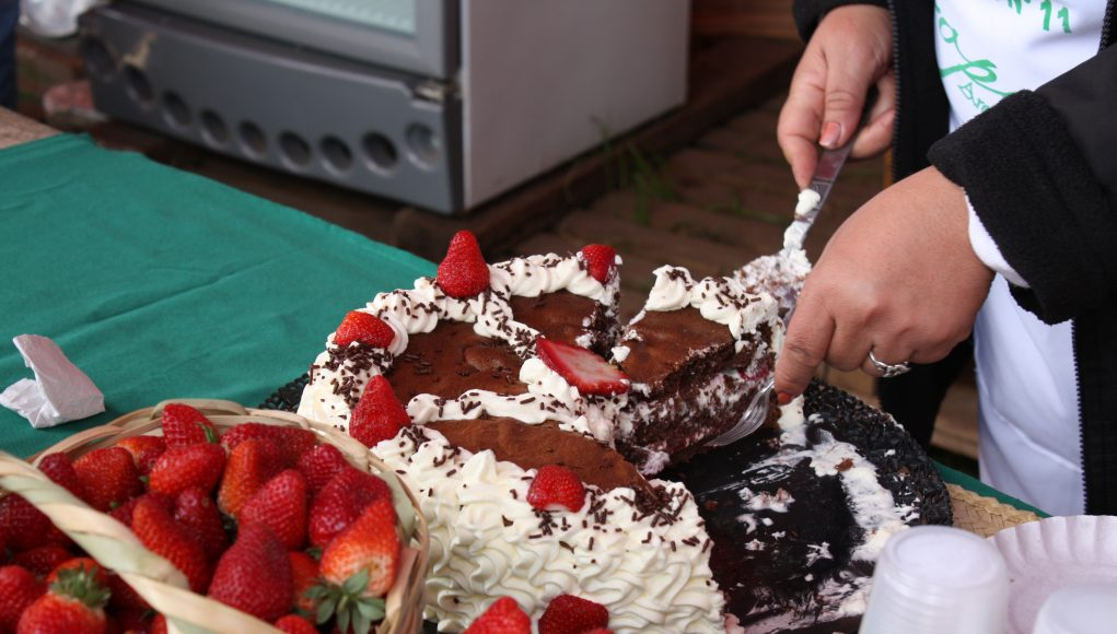 A person cutting a cake with fruit on top of a table