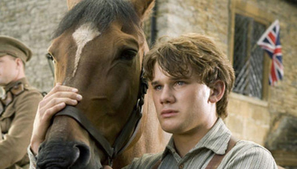 Jeremy Irvine petting a horse